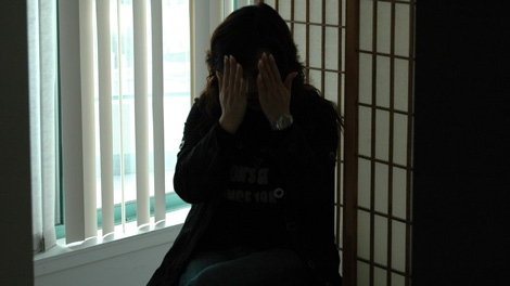 A Hong Kong native, shown during a 2010 police raid of a brothel, whom police believe was forced into the sex trade by Jian Feng Li. (Handout)