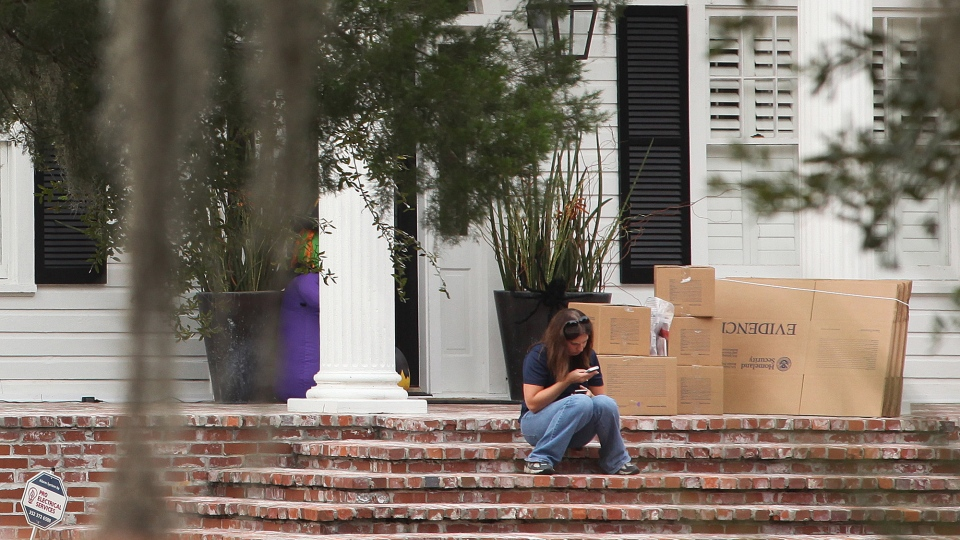 A woman uses her cell phone near evidence boxes as agents with the Department of Homeland Security collect evidence at the home of Eric Prokopi, a self-described