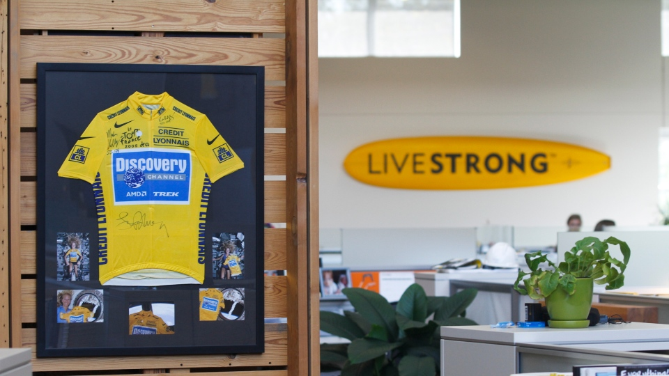 An autographed cycling jersey hangs in the offices of Livestrong, Lance Armstrong's cancer-fighting charity, Wednesday, Oct. 17, 2012, in Austin, Texas. (AP / Jack Plunkett)
