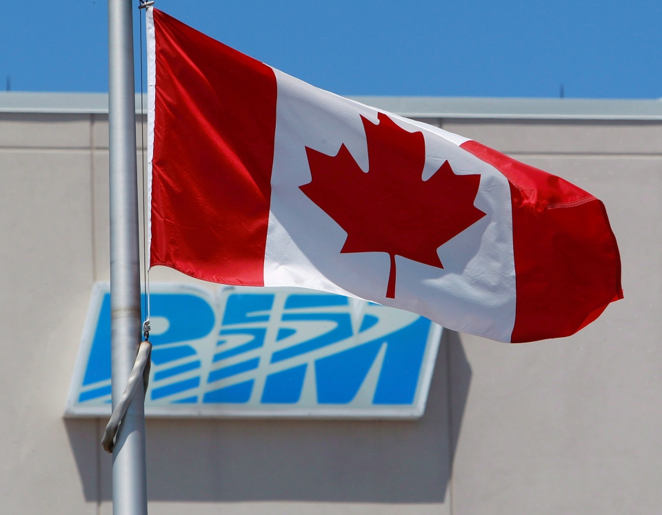 The Canadian flag flies in front of the Research In Motion (RIM) company logo on one of their buildings in Waterloo, Ont., on June 29, 2012. (Dave Chidley / THE CANADIAN PRESS)