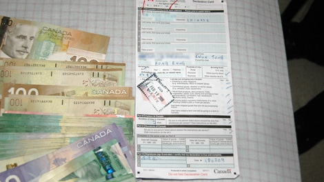 Cash and immigration papers seized during the raid of a brothel police believe is connected to Jian Feng Li. (Handout)