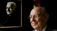Brother Jacques Berthiaume poses for a photograph next to a portrait of Brother Andre Bessette in Montreal, Friday, Oct. 8, 2010. (Graham Hughes / THE CANADIAN PRESS)