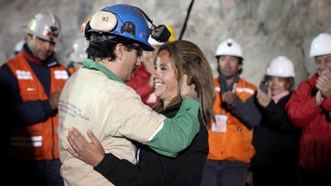 In this photo released by the Chilean government, miner Raul Bustos, left, embraces an unidentified woman after after being rescued from the collapsed San Jose gold and copper mine where he had been trapped with 32 other miners for over two months near Copiapo, Chile, Wednesday Oct. 13, 2010. (AP / Chilean Government, Hugo Infante)