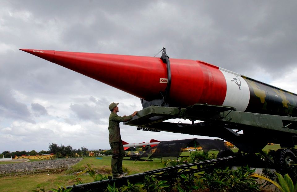 A soldier pauses to look at the outer casing of an old empty Soviet missile on exhibit as he works to paint it at the military complex Morro Cabana which is open to tourists in Havana, Cuba, Saturday, Oct. 13, 2012. (AP / Ismael Francisco, Cubadebate)