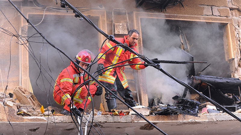 Lebanese rescue workers, remove rubble from a building that was damaged by an explosion in the mostly Christian neighborhood of Achrafiyeh, Beirut, Lebanon, Friday Oct. 19, 2012. (AP / Ahmad Omar)