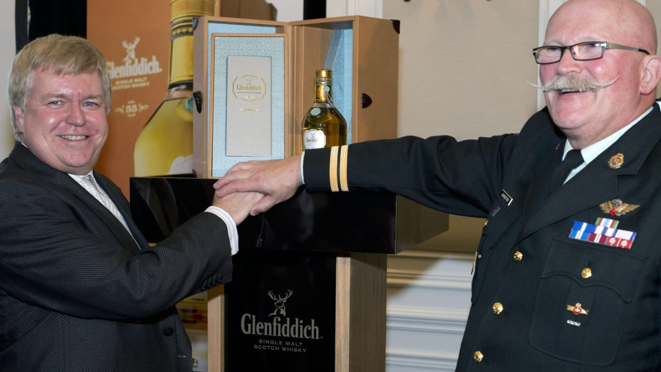 Dave from Toronto poses with Wayne Johnston, founder of Wounded Warriors (right) and 55-year-old Glenfiddich single malt Scotch in Toronto, Friday, October 19, 2012, after a record-breaking bid of $52,000.  (MARKETWIRE PHOTO/Glenfiddich Single Malt Scotch)