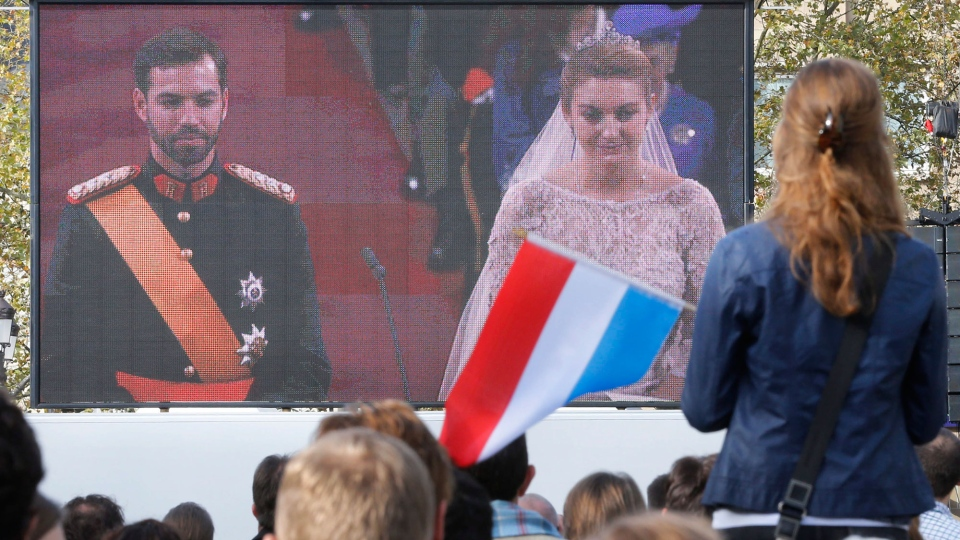 A girl waves a Luxembourg flag is she watches the royal wedding in the cathedral on a video screen on a square in Luxembourg, Saturday, Oct. 20, 2012. (AP / Michael Probst)