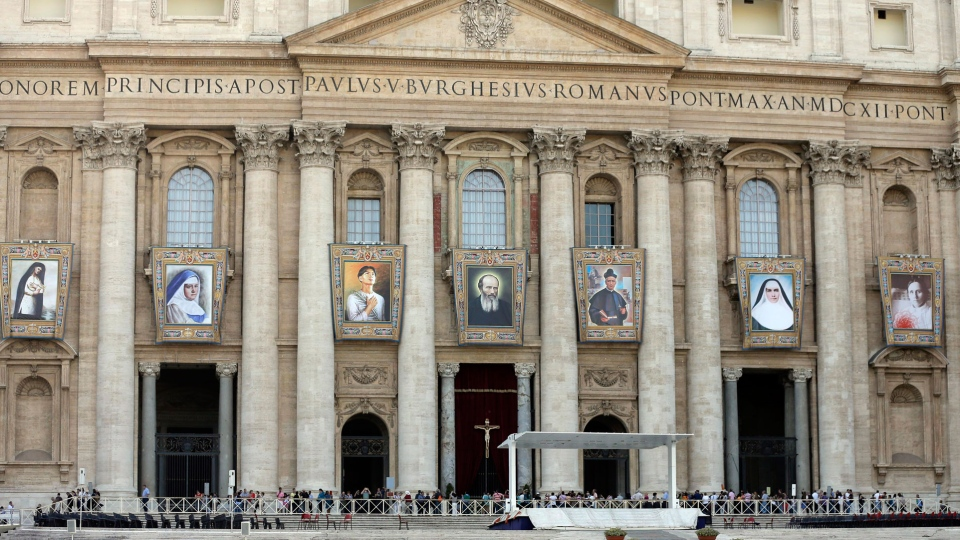 Tapestries of saints-to-be from left; Kateri Tekakwitha, Maria del Carmen, Pedro Calungsod, Jacques Berthieu, Giovanni Battista Piamarta, Mother Marianne Cope, and Anna Shaeffer hang from St. Peter's Basilica at the Vatican, Friday, Oct. 19, 2012. (AP / Alessandra Tarantino)