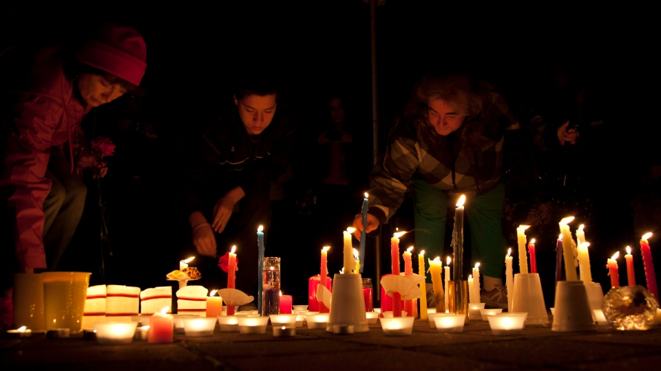 People place candles during a memorial for Amanda Todd in Surrey, B.C., Friday, Oct. 19, 2012. (Jonathan Hayward / THE CANADIAN PRESS)