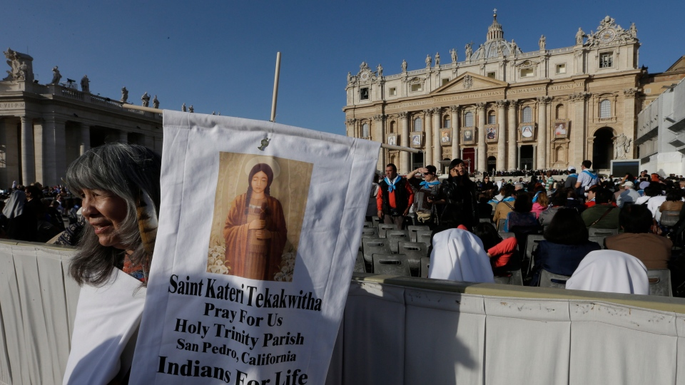 Clementine Little Hawk Fernandez, a Sioux of South Dakota, holds a banner of Kateri Tekakwitha before Pope Benedict XVI celebrates a canonization ceremony, in St. Peter's Square, at the Vatican, Sunday, Oct. 21, 2012. (AP / Alessandra Tarantino)