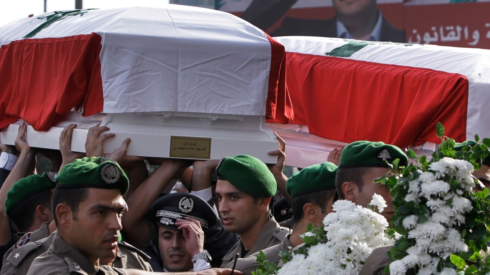 Members of Lebanese police intelligence division units carry the flag-draped coffins of Brig. Gen. Wissam al-Hassan and his bodyguard, who were assassinated on Friday by a car bomb, during their funeral procession at Martyrs' Square in Beirut, Lebanon, Sunday Oct. 21, 2012. (AP / Hussein Malla)