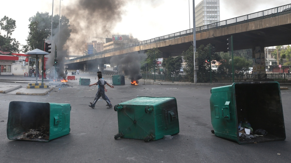 Lebanese citizens cross between burning tires and garbage containers laid by Sunni protesters after overnight clashes between Sunni and Shiite gunmen, in Beirut, Lebanon, Monday Oct. 22, 2012. (AP / Hussein Malla)