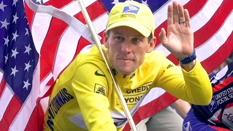 Tour de France winner Lance Armstrong rides down the Champs Elysees with an American flag after the 21st and final stage of the cycling race in Paris, France, July 23, 2000. (AP / Laurent Rebours)
