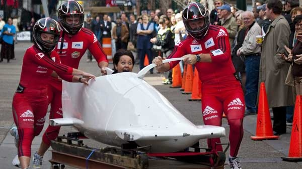Canadian bobsled team athletes push Calgary mayoral candidate Barb Higgins in a bobsled for a city block during a race between candidates Barb Higgins and Craig Burrows in Calgary, Tuesday, Oct. 12, 2010. (Jeff McIntosh/THE CANADIAN PRESS)
