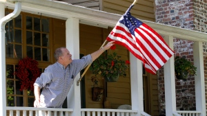 This photo taken Oct. 10, 2012 shows Virginia voter Harry Donahue adjusting an American flag on the front porch of his farmhouse, built in the 1700's, in Farmville, Va. (AP Photo / Steve Helber)