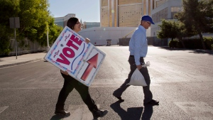 Election workers Elena Soto, left, and Dave Carlson post early voting signs for a polling place along Frank Sinatra Blvd. behind The Mirage Hotel-Casino in Las Vegas on Oct. 20, 2012. (AP Photo / Julie Jacobson)