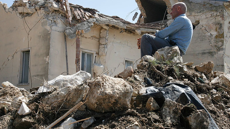 A man sits on rubbles in the village of Onna, a day after a powerful earthquake struck the Abruzzo region in central Italy on April 7, 2009.  (AP /Alessandra Tarantino)