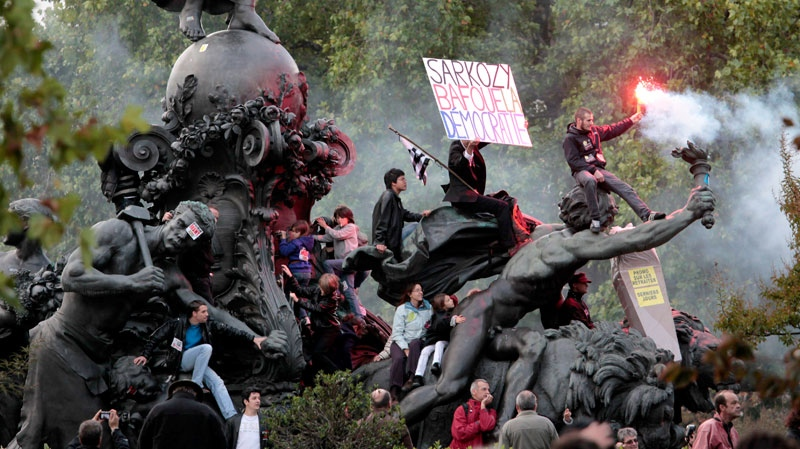 Protestors climbed on a statue during a demonstration in Paris with placard reading, 'Sarkozy scorns the democracy,' Saturday, Oct. 16, 2010. (AP / Thibault/Camus)