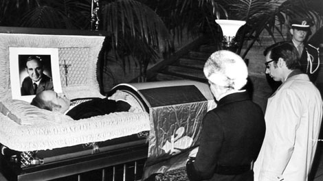 The body of Pierre Laporte, with Premier and Mrs. Robert Bourassa kneeling before it, lies in state Monday, Oct. 20, 1970 in the Montreal courthouse, attended by an honour guard of provincial police. An author of Quebec's high-school history textbooks casts the federal government as the main villain of the October Crisis 40 years ago, disputes that Pierre Laporte  was murdered, and defends the terrorist FLQ whose victims were, he says, mere �collateral damage� in the greater cause of independence. THE CANADIAN PRESS/