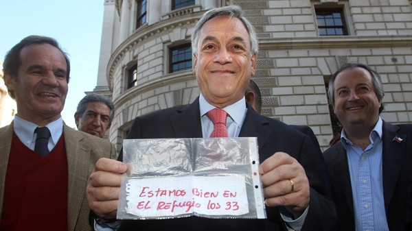 Chilean President Sebastian Pinera holds the original message passed from the entombed miners to rescuers, informing those above that there are 33 miners alive inside the San Jose mine in Chile, following a visit to the Cabinet War Rooms in central London, Sunday Oct. 17, 2010. (AP / Lewis Whyld)