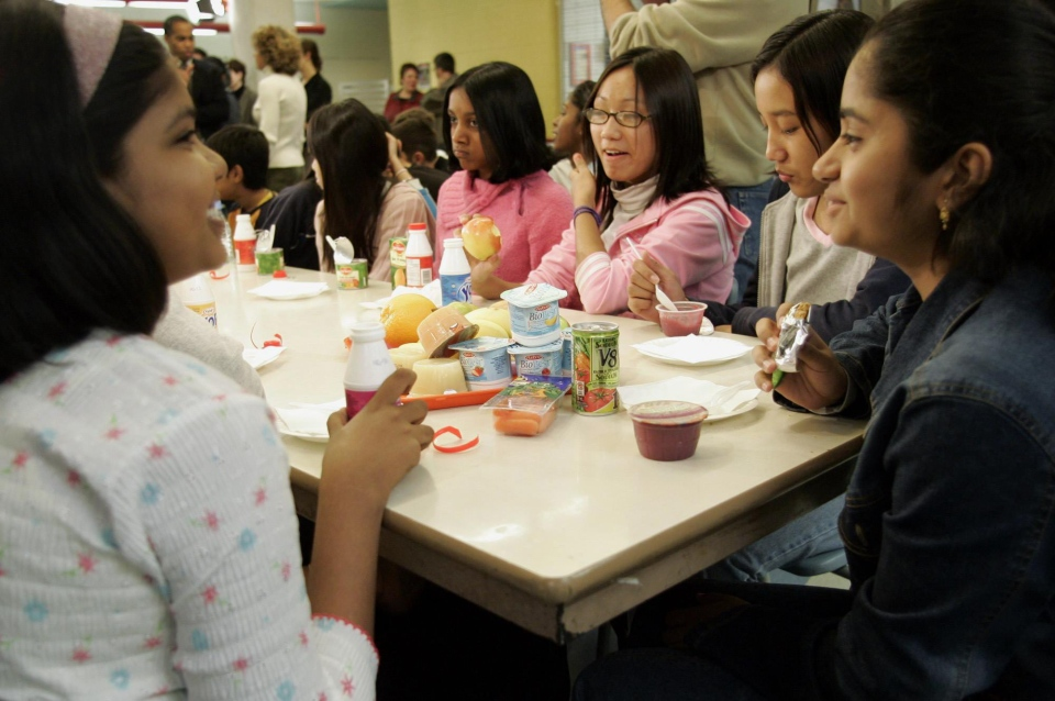 In this October 2004 file photo, children at an elementary school in Toronto eat healthy snacks in the cafeteria. (CP / Adrian Wyld)