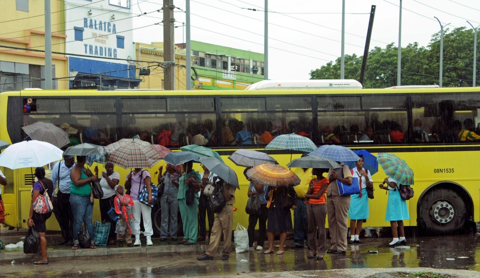 Commuters wait at a bus stop as rain brought by the outer bands of Tropical Storm Sandy falls in Kingston, Jamaica, Tuesday, Oct. 23, 2012. (AP / Collin Reid)