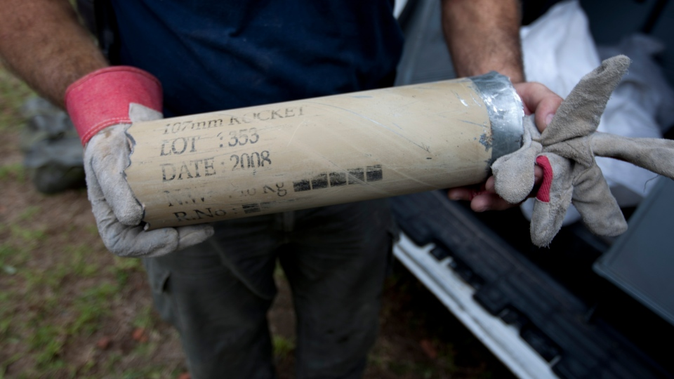An Israeli police sapper holds the remains of a rocket rocket fired by Palestinian militants after it hit a community along the Israel Gaza Border, southern Israel, Wednesday, Oct. 24, 2012. (AP Photo/Ariel Schalit)