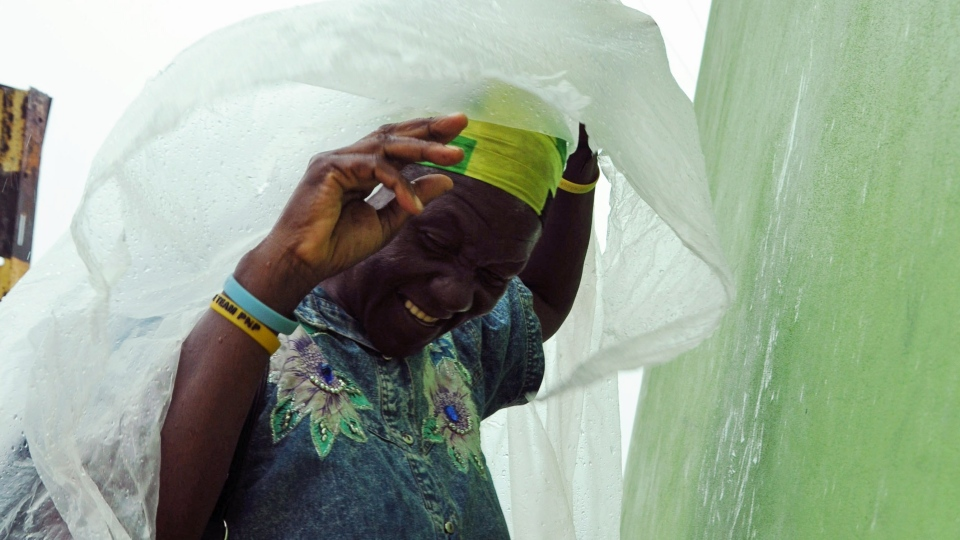 Pauline Daley covers herself as rain brought by the outer bands of Tropical Storm Sandy falls in Kingston, Jamaica, Tuesday, Oct. 23, 2012. (AP / Collin Reid)