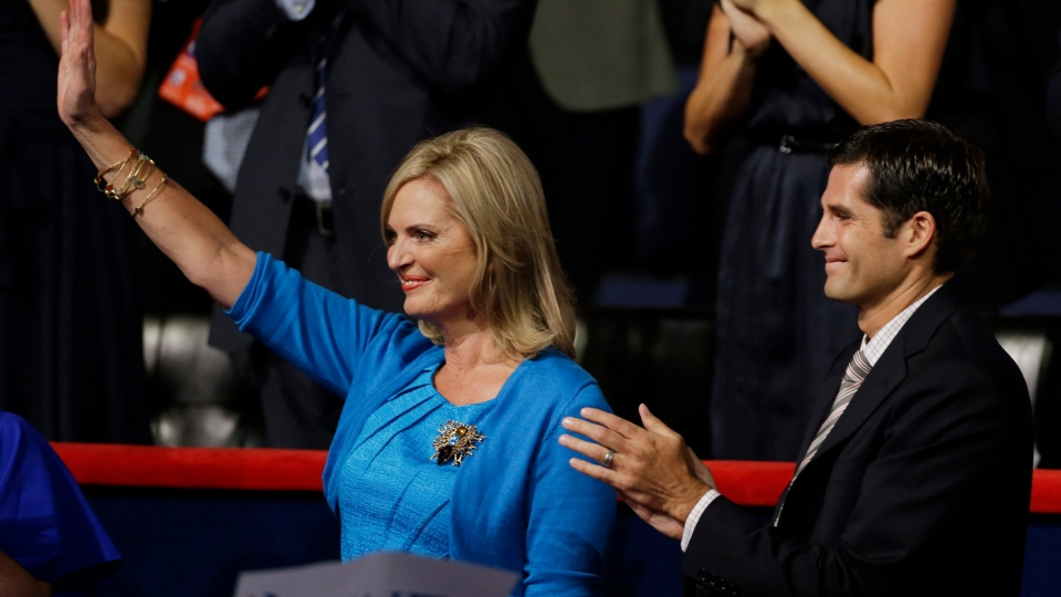 Ann Romney waves with her son Tagg as Republican presidential nominee Mitt Romney addresses delegates during the Republican National Convention in Tampa, Fla., on Thursday, Aug. 30, 2012. (AP / Charlie Neibergall)