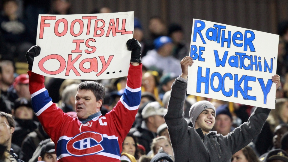 Fans hold signs commenting on the NHL lockout during first half CFL action between the B.C. Lions and Hamilton Tiger-Cats, in Hamilton on Friday, Oct. 12, 2012. (Dave Chidley / THE CANADIAN PRESS)