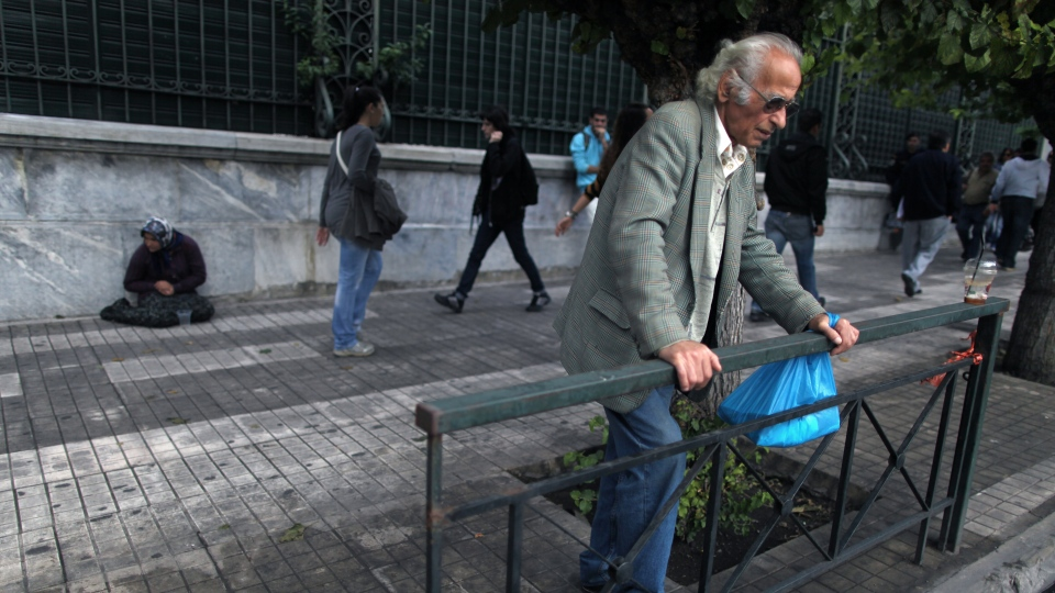 A man stands in front of a beggar in Athens on Wednesday, Oct. 24, 2012. (AP / Petros Giannakouris)