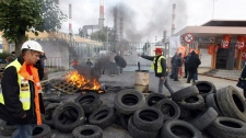 French Union workers burn tires to block the entrance of the oil refinery of Grandpuits eastern of Paris, Monday, Oct. 18, 2010. (AP Photo/ Francois Mori)
