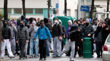 Youth throw items to police officers during clashes in Nanterre, outside Paris, Tuesday, Oct. 19, 2010.  (AP / Thibault Camus)