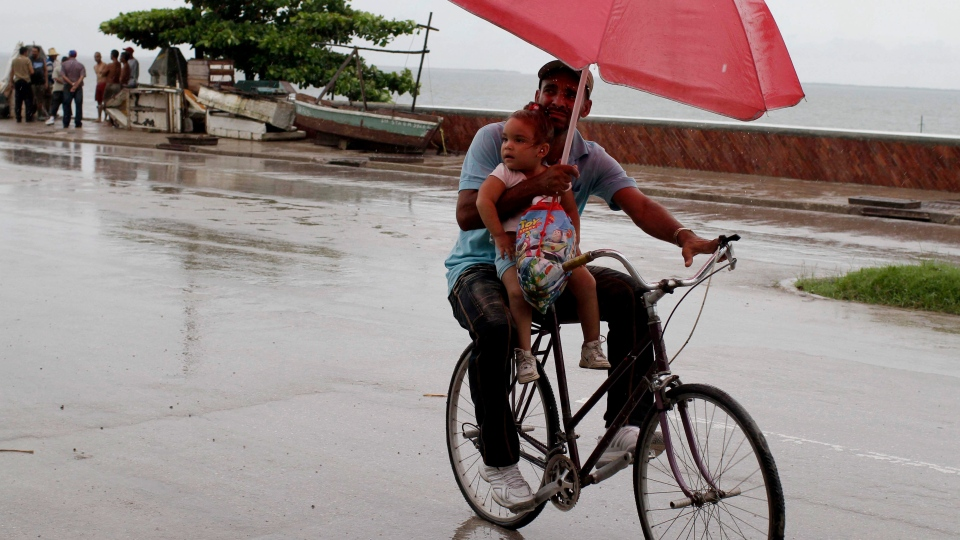 A man balances a child and umbrella on his bike as it rains during the approach of Hurricane Sandy in Manzanillo, Cuba on Wednesday, Oct. 24, 2012. (AP / Franklin Reyes)
