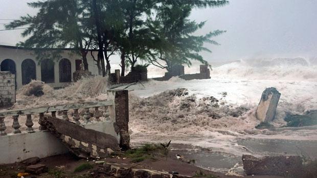 Waves, brought by Hurricane Sandy, crash on a house in the Caribbean Terrace neighborhood in eastern Kingston, Jamaica, on Wednesday, Oct. 24, 2012. (AP / Collin Reid)
