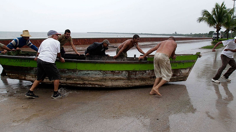 People remove a boat from the water ahead of the arrival of Hurricane Sandy in Manzanillo, Cuba, Wednesday, Oct. 24, 2012. (AP / Franklin Reyes)