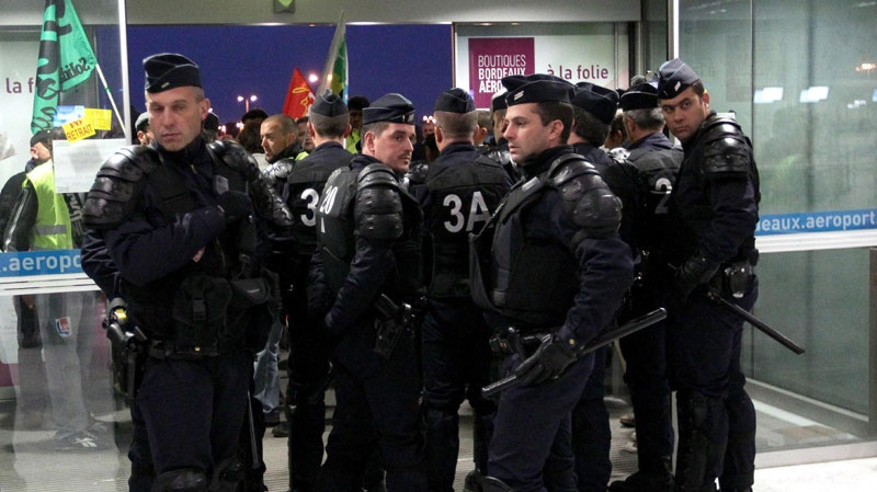 Demonstrators with trade union flags are blocked by french riot police at the Merignac airport, near Bordeaux, southwestern France, Tuesday Oct. 19, 2010. (AP Photo/Bob Edme)