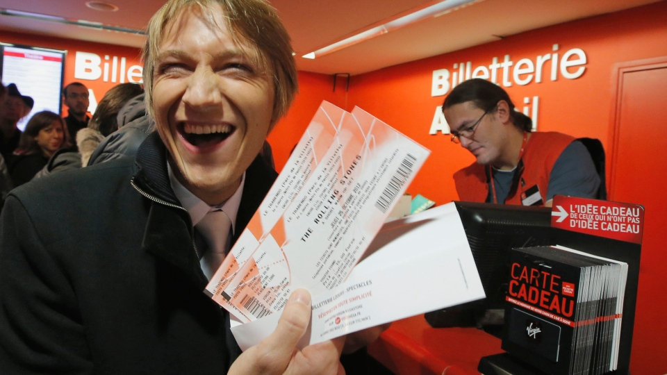 Michael Evanno, 31, shows the tickets he bought for the Rolling Stones concert at Virgin Megastore in Paris, Thursday Oct. 25, 2012. The Rolling Stones announced a surprise