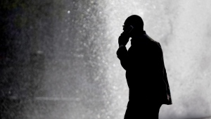 A pedestrian talking on a mobile phone is silhouetted in front of a fountain at John F. Kennedy Plaza, Thursday, Oct. 11, 2012. (AP / Matt Rourke)