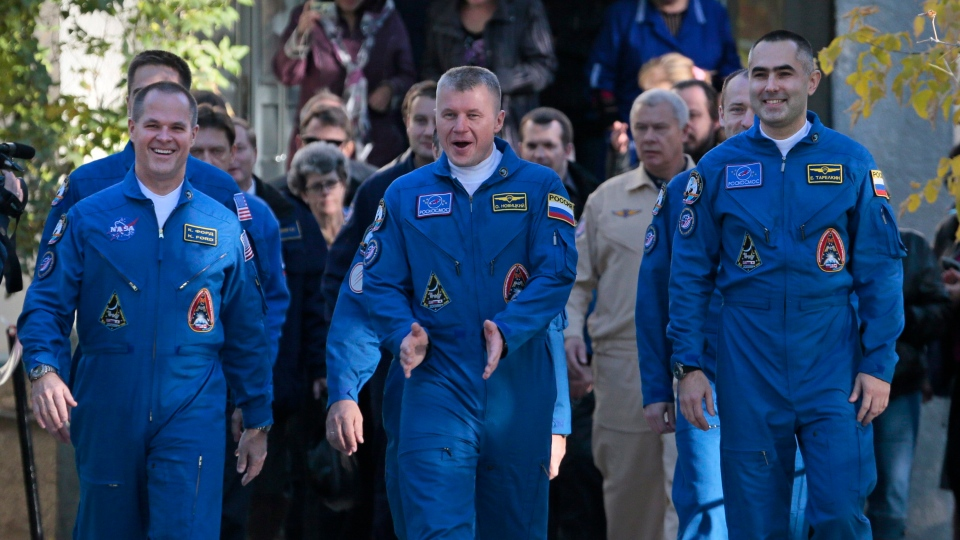U.S. astronaut Kevin Ford, left, and two Russian cosmonauts Oleg Novitsky, center, and Yevgeny Tarelkin, right, walk away from their base to the bus that will take them to the launch pad prior the launch of Soyuz-FG rocket booster with Soyuz TMA-06M space ship at the Baikonur cosmodrome, Kazakhstan, Tuesday, Oct. 23, 2012. (AP / Mikhail Metzel)