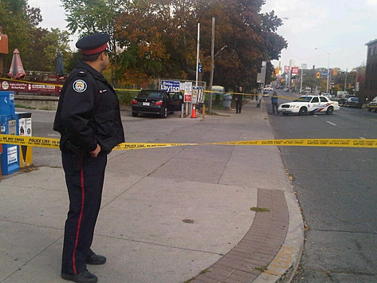 Toronto police watch over the crime scene at Bloor St. W. and Crawford St. on Wednesday, Oct. 20, 2010. (Keith Hanley/CTV News)