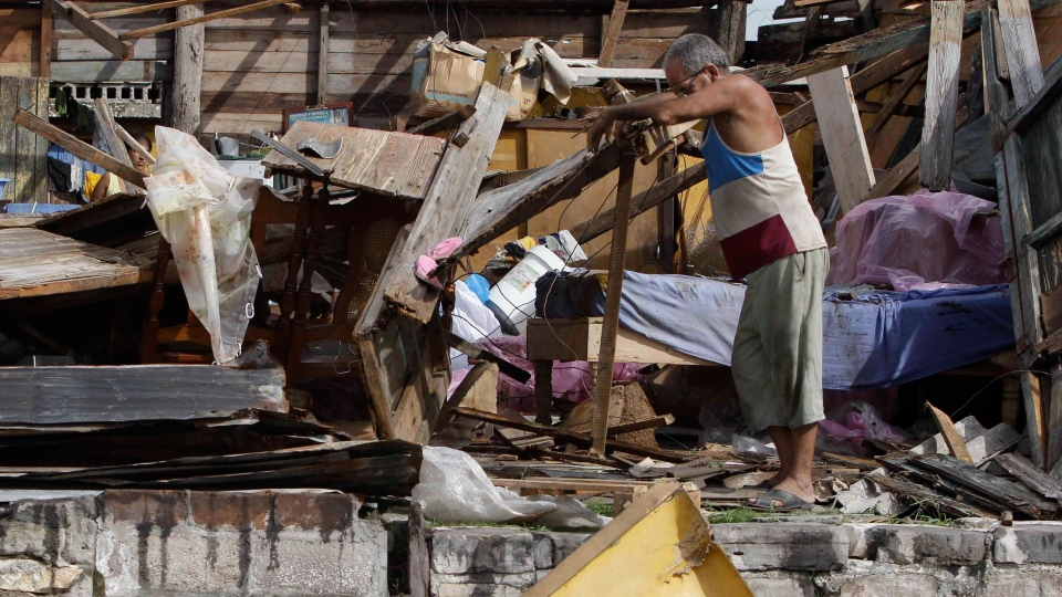 Resident Antonio Garces tries to recover his belongings from his house destroyed by Hurricane Sandy in Aguacate, Cuba, Thursday Oct. 25, 2012. (AP / Franklin Reyes)