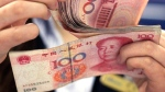 In this file photo taken on Aug. 25, 2010, a bank clerk counts Chinese 100 Yuan notes in Shanghai. (AP Photo/Eugene Hoshiko)