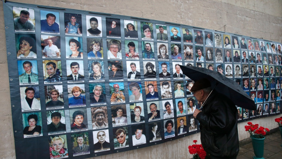 A man stands in front of portraits of victims of a theatre siege in Moscow, Russia, Friday, Oct. 26, 2012. (AP / Misha Japaridze)