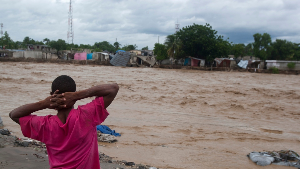 A man watches a river affected by heavy rains brought by Hurricane Sandy in Port-au-Prince, Haiti, Thursday, Oct. 25, 2012. (AP / Dieu Nalio Chery)