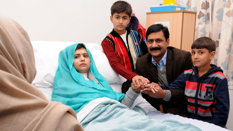 Malala Yousufzai is shown in her hospital bed with her father Ziauddin, second right accompanied by her two younger brothers Atal, right and Khushal, centre, in this undated handout photo issued by Queen Elizabeth Hospital, in Birmingham, England, on Friday, Oct. 26, 2012. (AP / Queen Elizabeth Hospital Birmingham)