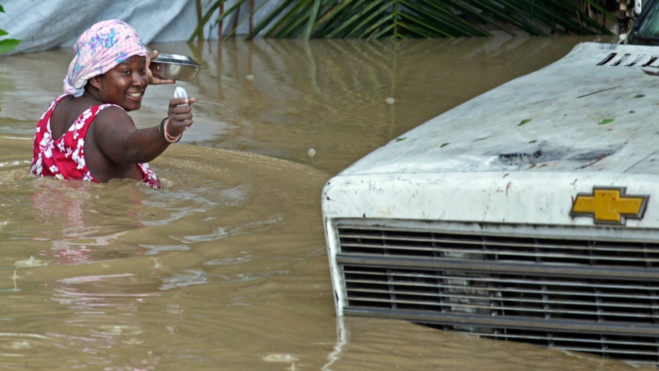 A woman makes her way to her home as the water level continues to rise in Leogane, Haiti, Friday, Oct. 26, 2012.  (AP / The Miami Herald, Carl Juste)