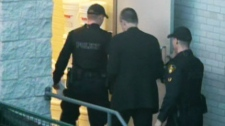 Col. Russell Williams is escorted by police as he arrives at a Belleville, Ont., court on Thursday, Oct. 21, 2010.