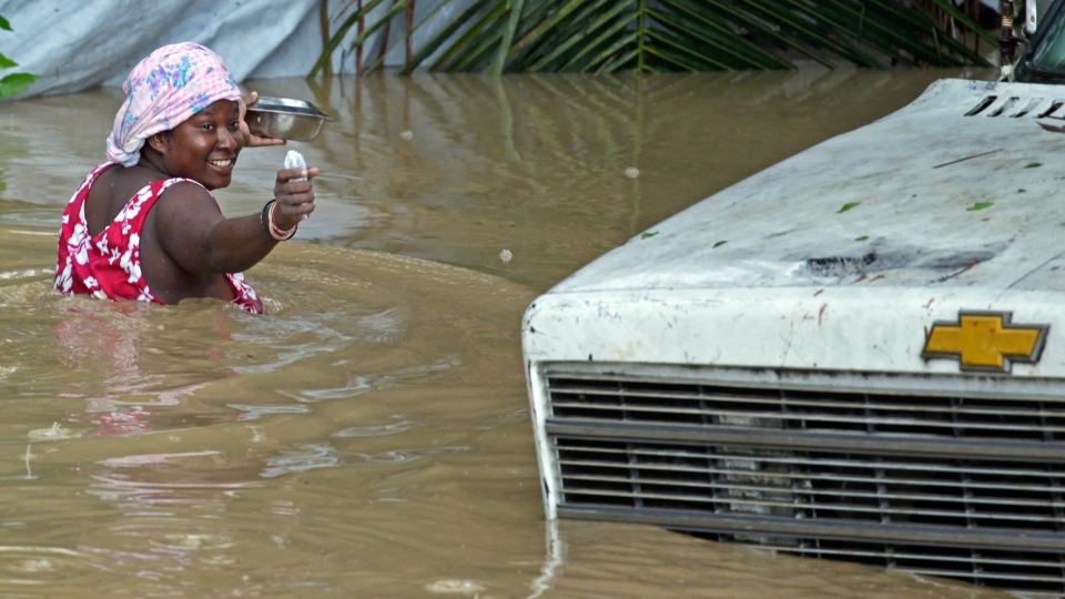 A resident of Leogane, Haiti makes her way to her home as the water level continues to rise on Friday, Oct. 26, 2012. (AP /The Miami Herald, Carl Juste)