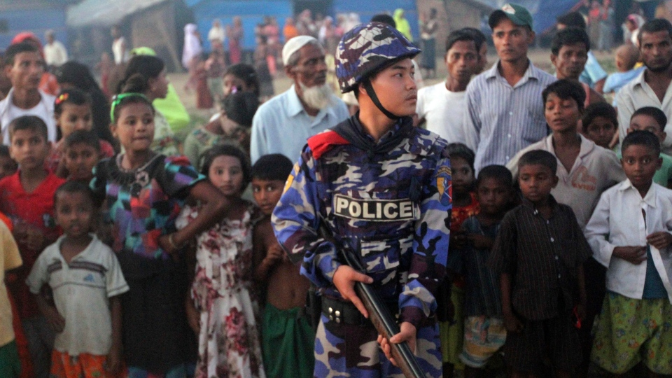An armed police officer guards as Muslim refugees stand behind him at a refugee camp in Sittwe, capital of Rakhine State, western Myanmar on Saturday, Oct. 27, 2012.  (AP / Khin Maung Win)